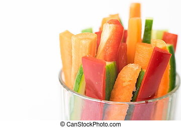 Close up of colorful vegetable sticks in a glass isolated on white background