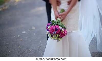 Close Up of Colorful Wedding Bouquet at Bride's Hands and Groom on Background