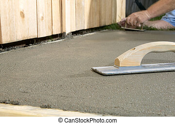 Close up of concreting tools and wet cement slab