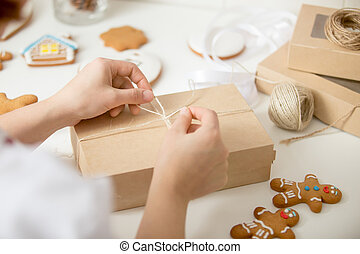 Close up of confectioner hands wrapping a cardboard box -...