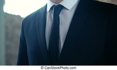Close-up of confident businessman adjusting his necktie and jacket.