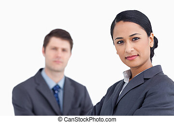 Close up of confident saleswoman with co-worker behind her
