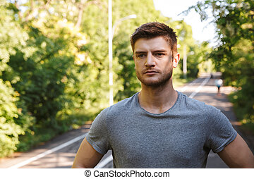 Close up of confident sportsman standing on a road