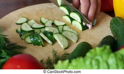 Close-up of cook cutting fresh cucumber on wooden chopping Board, slow motion.