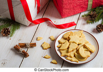 Close-up of cookies with Christmas gifts on old wooden table