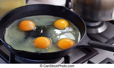 Close-up of cooking fried eggs in black cast-iron frying pan...