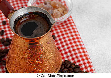 Close up of copper coffee turk on light textured surface