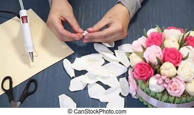 Close-up of corrugated paper hack bright pink in female hands. Female decorator folds of paper origami flower button. Modern art: making crafts out of paper to decorate parties, weddings and march 8