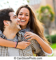 Close up portrait of happy laughing couple having fun outdoors.