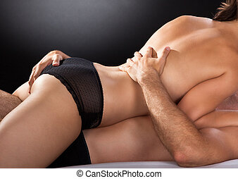 Close-up of couple having sex isolated on colored background