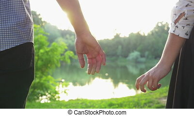 Close-up of couple holding hands at sunset and walking together