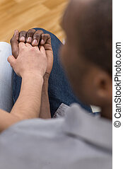 Close up of couple holding hands while sitting. over shoulder view of woman putting her hand on african man hand