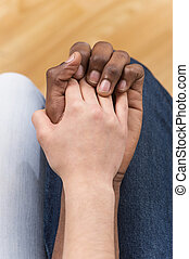 Close up of couple holding hands while sitting. top view of woman putting her hand on african man hand
