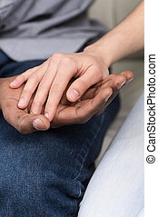 Close up of couple holding hands while sitting. woman putting her hand on african man hand