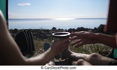 Close-up of couple in tent drinking coffee - Close-up of...