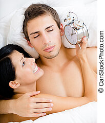 Close up of couple lying in bed with alarm clock