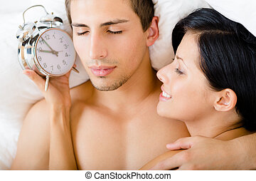 Close-up of couple lying in bed with alarm clock