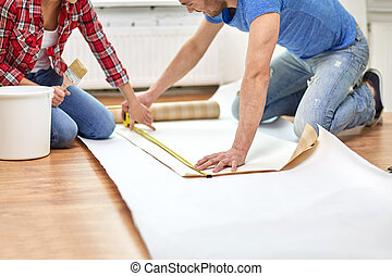 close up of couple measuring wallpaper - repair, building...
