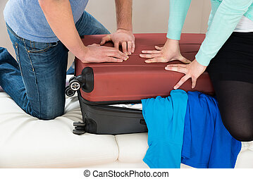 Couple Together Packing Luggage