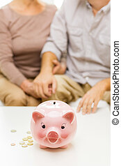 close up of couple with coins and piggy bank