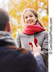 love, family, autumn and people concept - close up of smiling couple with engagement ring in small red gift box outdoors