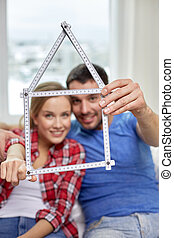 close up of couple with house shape ruler - people, real...
