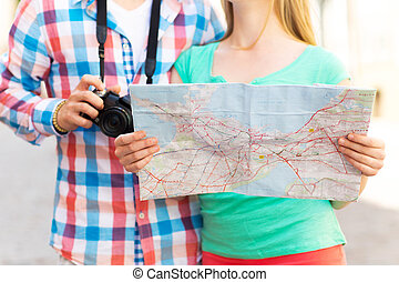 close up of couple with map and camera in city