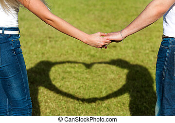 Close up of couples hands together with love sign.