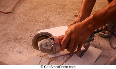Close up of craftsman is cutting floor tile with portable angle grinder.