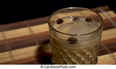 creamy coffee alcoholic cocktail with beans in a glass