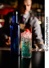 close-up of crysyal glass of cold blue alcoholic cocktail and bottle on bar