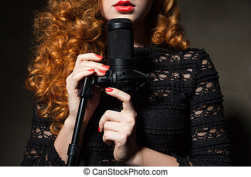 Close-up of curly-haired woman with mic