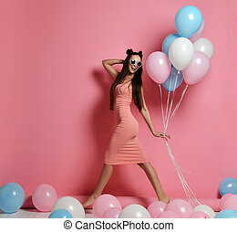 Close-up of cute blond girl standing in a studio, smiling widely and playing with blue and pink baloons.