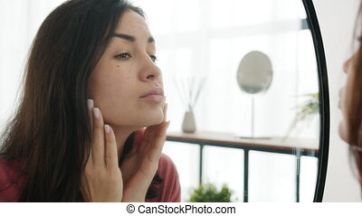Close-up of cute girl looking at mirror in bathroom looking for imperfections on skin touching face with fingers. Beauty oriented people and lifestyle concept.