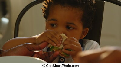 Close-up of cute little black son eating food at dinning table in kitchen of comfortable home 4k