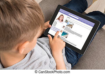 Cute Little Boy Using Social Networking Site On Digital Tablet