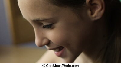 Close-up of cute little girl using application on digital tablet in her hands