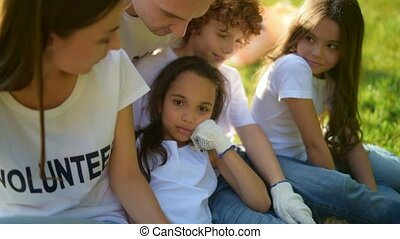 Close up of cute pensive children resting with volunteers