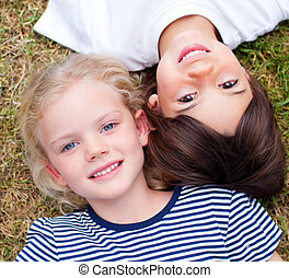Close-up of cute siblings lying on the grass in a park