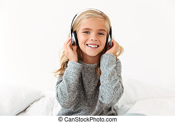 Close-up of cute smiling girl in headphones sitting in bed, looking at camera