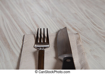 Close up of cutlery on wooden table. Stainless steel fork and knife