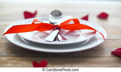 close up of cutlery tied with red ribbon on plate -...