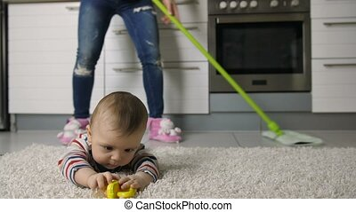 Close-up of female legs mopping dirty kitchen floor and dancing while baby playing on the carpet. Busy cheerful housewife doing housework near her sweet infant son at home. Dolly shot.