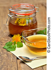 Close-up of dandelion honey in a glass bowl and dandelion head around, full jar in background - vertical photo