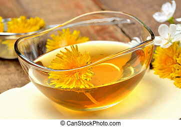 Close-up of dandelion honey in a glass bowl and dandelion head around
