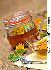 Close-up of dandelion honey, spoon, dandelion head around and full jar in background - vertical photo