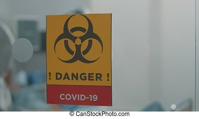 Close up of danger sign against coronavirus outbreak in hospital ward. Infectious zone in isolation and quarantine against covid 19 pandemic with biohazard symbol on glass. Lockdown virus area