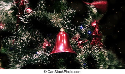 Close up of decorated Christmas tree at night with red bell,...