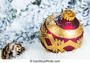 Close up of decorative Christmas ball on the snow and Christmas tree as a background.