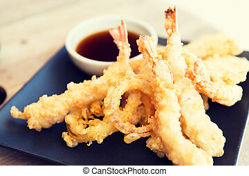 close up of deep-fried shrimps and soy sauce